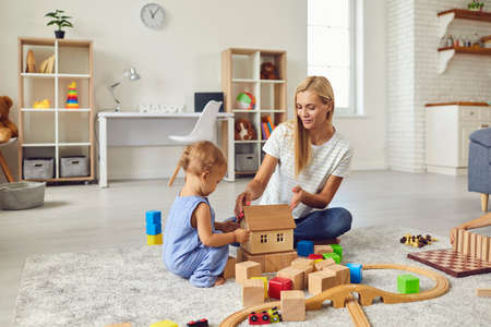 Photo pour Mom and child at home. Young mother playing with little son teaching him to build toy house. Happy nanny engaging toddler boy in fun activities with wood blocks on warm floor in cozy studio apartment - image libre de droit