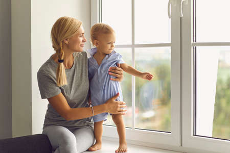 Photo pour Young mother and little son looking out large new window. Happy mom and child relaxing at home. Babysitter hugging curious toddler who exploring the world and observing neighborhood from windowsill - image libre de droit