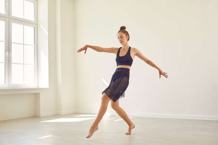 Photo for Concentrated young female dancer practicing alone in new modern studio. Serious barefoot girl rehearsing dance elements preparing for upcoming competition or contemporary dance event - Royalty Free Image