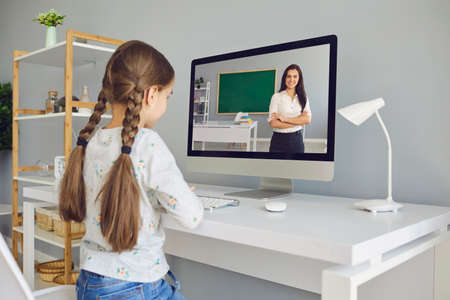 Foto de Distance learning education. A little girl listens to a teacher video lecture online in a laptop at the table at home. The teacher teaches the child from the computer. - Imagen libre de derechos