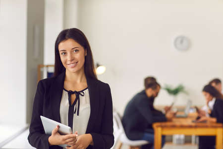 Photo pour Happy smiling female company president holding tablet computer standing in office looking at camera. Portrait of young woman, successful business leader, in office workspace with busy employees behind - image libre de droit