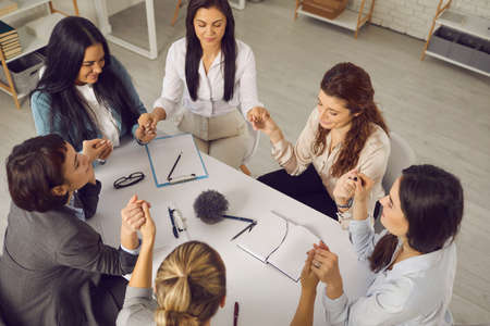 Photo pour Team of business women holding hands, sitting together around office table with eyes closed in group meeting or coaching session. Support, unity, understanding, empathy concept. From above, high angle - image libre de droit