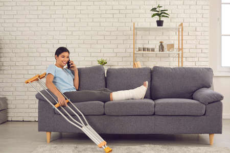 Photo pour Positive happy young woman with broken leg in plaster cast sitting on sofa with crutches at home, talking on mobile phone, telling friend or relative about accident which resulted in bone fracture - image libre de droit