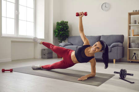 Home training. Athletic woman trains lying sideways on a sports mat and lifts up her leg and dumbbell. Athlete does not miss training while at home. Fitness, sport, training and lifestyle concept.