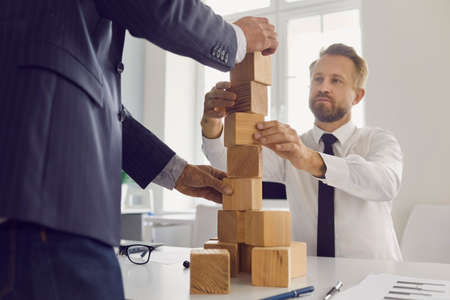 Photo for Mature and young businessmen making wood block tower as metaphor for building strong business together. Concepts of collaboration, succession, maintaining financial stability, economical growth - Royalty Free Image