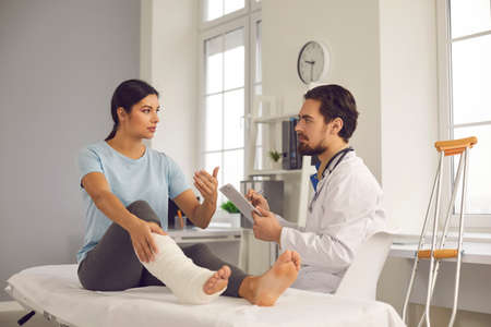 Photo pour Physical injury treatment: Serious doctor listening to patient with bone fracture. Young woman with broken leg talking to traumatologist or orthopedic surgeon during medical exam in hospital or clinic - image libre de droit
