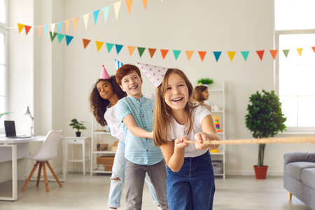 Foto de Childrens team in colored conical hats has fun and plays a game of tug of war at a festive childrens party in honor of the birthday. Multiethnic girls and boys celebrate together at home. - Imagen libre de derechos