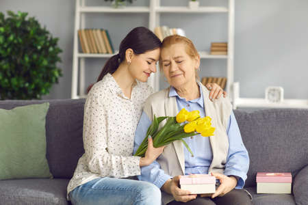 Photo pour Happy senior woman enjoying gifts on Mothers or International Womens Day. Loving young daughter gives old mom flowers and presents. Smiling granddaughter sitting on sofa with grandma and hugging her - image libre de droit