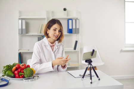 Photo pour Female nutritionist sits in her office and records a video for her blog using a tripod-mounted phone. Woman shares useful information about proper nutrition. Concept of modern technology and medicine. - image libre de droit