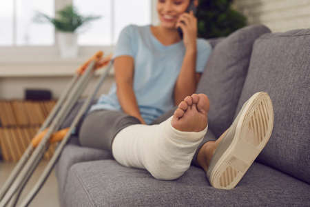 Photo pour Concept of rehabilitation of people with injury. Patient with broken leg resting on couch at home. Happy injured woman sitting on sofa and talking on mobile phone. Close-up of foot in plaster cast - image libre de droit