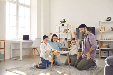 Photo pour Family weekend entertainment. Mom, dad, daughter and son play game sitting at a table from which a wooden tower falls. Fun board games for family leisure. Stay at home activity for kids. - image libre de droit