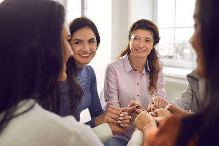 Photo pour Happy smiling young women sitting in circle and holding hands in corporate meeting or group session with motivational coach. Concept of female community, support and achieving goals together. Close-up - image libre de droit