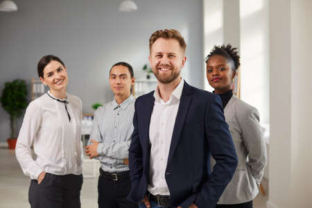 Foto für Successful international team, business development, Teamwork concept. Group of young smiling confident mixed race workers standing and looking at camera together in office - Lizenzfreies Bild
