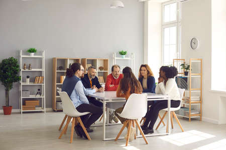 Photo pour Team of mixed race business people sitting around big table in modern office space. Group of diverse company employees discussing projects and taking decisions together in corporate meeting - image libre de droit
