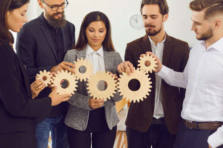 Photo pour Young company managers joining gearwheels as metaphor for effective management and collaboration - image libre de droit