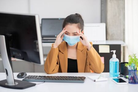 Photo pour Employees working in business office got headache and fever while wearing medical face mask for protecting and preventing the infection of corona virus or covid-19 - image libre de droit