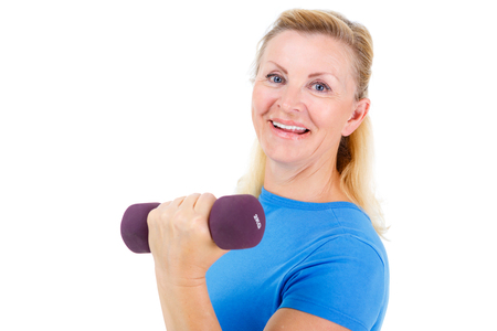 Pensioner woman sport. Old senior woman dressed in blue t-shirt. Woman looking at camera, holding dumbbells and cheerfully smiling while doing sport exercises. isolated on white backgroundの写真素材
