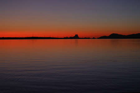 Foto de sunset view in front of the sea with the silhouette of a mountain in the background - Imagen libre de derechos