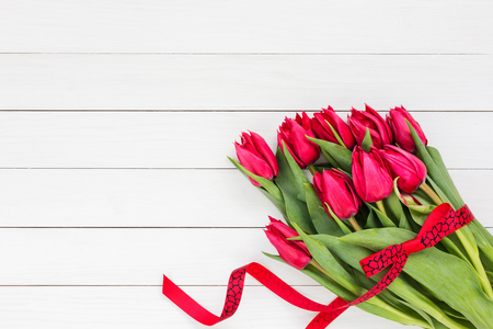 Photo pour Bouquet of red tulips with red ribbon on white wooden background. Top view, copy space - image libre de droit