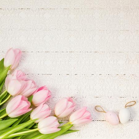 Photo pour Pink tulips and decorative Easter eggs on white tablecloth. Top view, copy space - image libre de droit