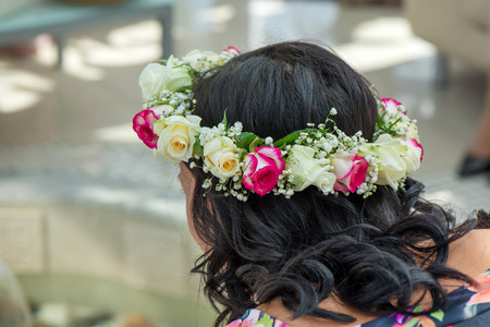 Female hair with beautiful colorful flower crown. Cheerful bride and bridesmaids party before wedding.