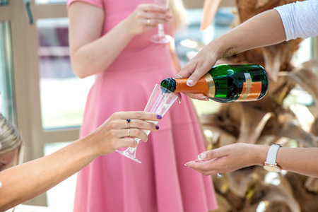 Group of girls in pink dress code celebrating - pouring champagne in glasses and drinking. Cheerful bride and bridesmaids party before wedding. Women having fun