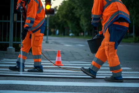 Traffic line painting. Workers are painting white street lines on pedestrian crossing. Road cones with orange and white stripes in background, standing on asphalt during road construction works
