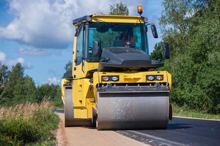 Foto de Yellow heavy vibration roller at asphalt pavement works. Road repairing in city. Road construction workers repairing highway road on sunny summer day. Heavy machinery, loaders and trucks. - Imagen libre de derechos