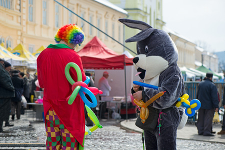 Foto de Giant Easter bunny mascot and a freelance clown creating balloon animals and different shapes at outdoor festival in city centre. - Imagen libre de derechos
