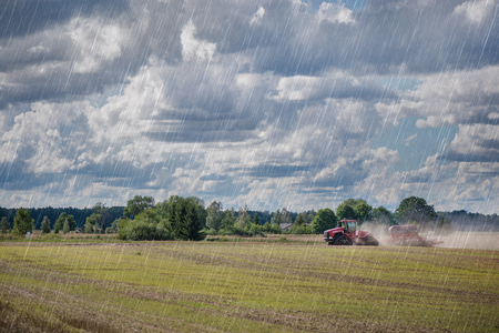 Photo pour Agricultural background. Red tractor pulling plow, throwing dust in air. Combine harvester at wheat field. - image libre de droit