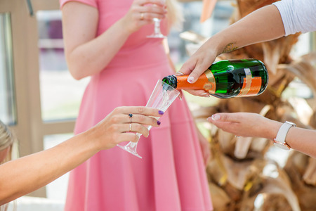 Group of girls in pink dress code celebrating  pouring champagne in glasses and drinking. Cheerful bride and bridesmaids party before wedding. Women having fun