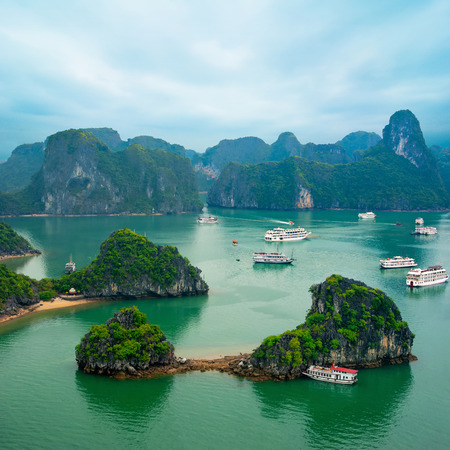 Tourist junks floating among limestone rocks at early morning in Ha Long Bay South China Se