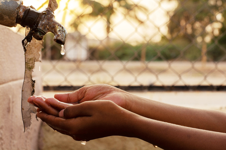 Photo pour Closeup of hands, child drinking water directly from corporation tap water in India. - image libre de droit