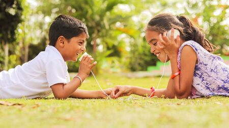 Photo pour Two children having fun by playing with String Telephone at park during vacation - Concept of brain development and socializing by playing outdoor games in the technology driven world. - image libre de droit
