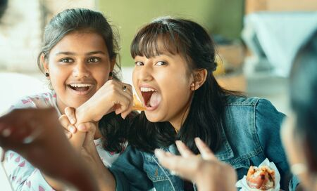 Photo pour Teenager trying to take or grab food from friend - young girl playfully fighting for snacks with her friend - concept of friends having fun while having food at college restaurant. - image libre de droit