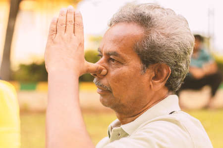 Photo for Closeup of of senior man doing alternate Nostril Breathing exercise or nadi shodhana pranayama at park - Concept of healthy active old people lifestyle. - Royalty Free Image