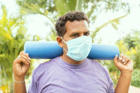 Foto de Fat man wearing medical face mask holding yoga mat on shoulder came for exercise after quarantine to park - concept of life after coronavirus or covid-19 lockdown and new normal - Imagen libre de derechos