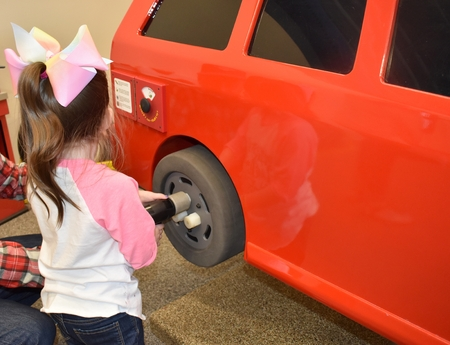 Toddler working on her toy car