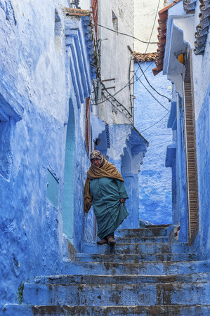 A woman in typical moroccan clothing, walking down a street in the blue Medina of Chefchaouen