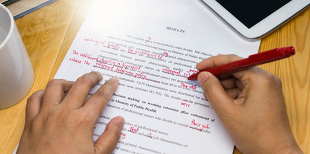 Photo pour hand holding red pen over proofreading text on table - image libre de droit