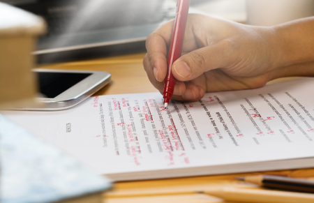 Photo pour hand holding red pen over proofreading text in office - image libre de droit