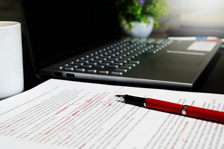 Photo pour blur proofreading sheet on table with red pen and laptop - image libre de droit