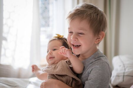 Photo pour little infant baby girl sitting together with her toddler brother - image libre de droit
