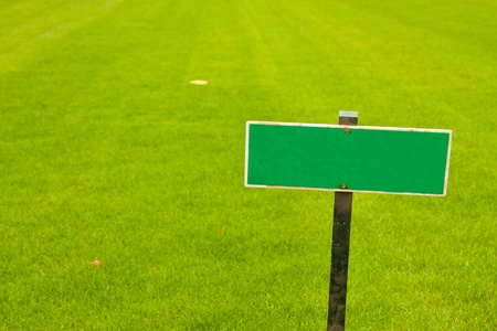 Green grass with a sign, horizontal shot with copy space