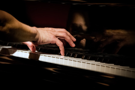 Photo pour Playing piano at concert, focus on right hand, close up at low light conditions - image libre de droit