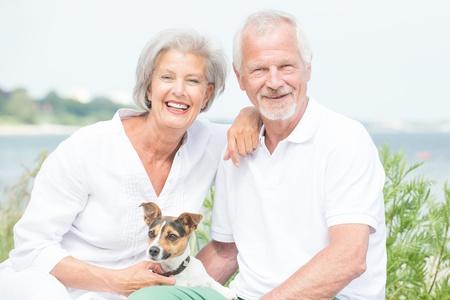Foto de Smiling and actice senior couple with dog - Imagen libre de derechos