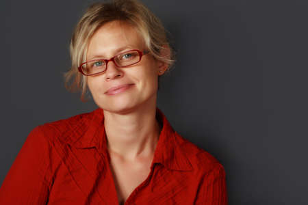 portrait of a blond woman wearing red glasses and red shirt