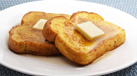 french toast with piece of butter on a white plate