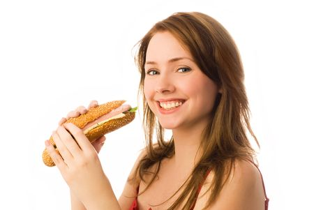 happy young woman eating a hot dog isolated against white background