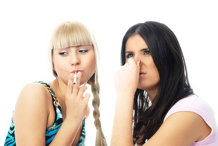 portrait of two young women, one of them is going to smoke a cigarette and the other frowns and closes her nose